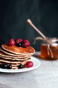 Сочные блины с ягодами и медом на белой тарелке, ложке, банке, деревянном столе.