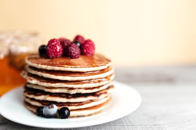 Сочные блины с ягодами и медом на белой тарелке, ложке, банке, деревянном столе