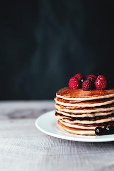 Сочные блины с ягодами и медом на белой тарелке, ложке, деревянном столе. фото высокого качества