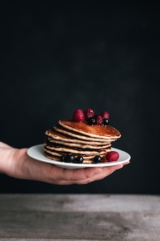 Сочные блины с ягодами и медом на белой тарелке на руке человека, деревянном столе. фото высокого качества