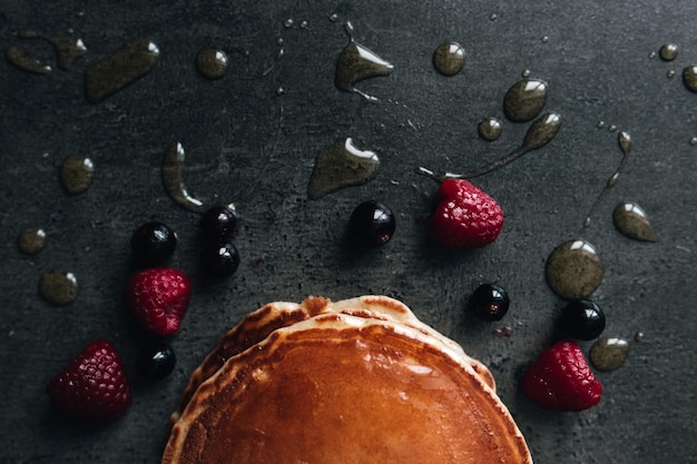 Juicy pancakes with berries, honey, spoon on a black and gray concrete table. high quality photo