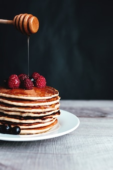 Juicy pancakes with berries and honey on a white plate, spoon, wooden table. high quality photo