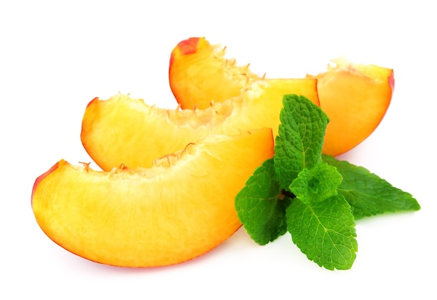 Сочные дольки персика с мятой крупным планом