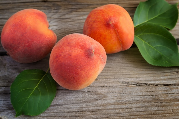 Juicy peaches on old wooden background. selective focus