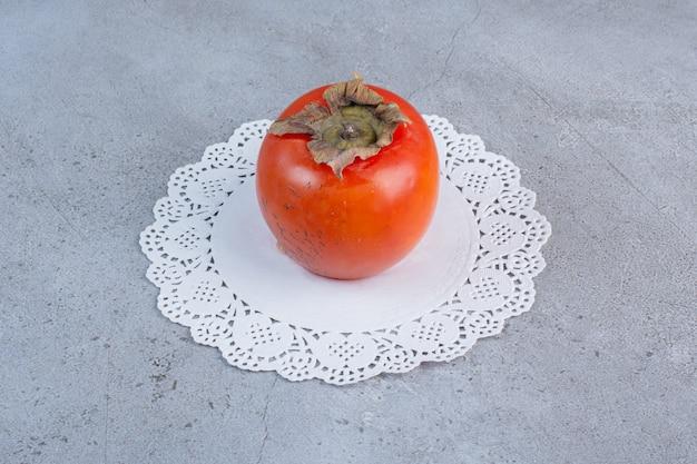 大理石の背景のドイリーにジューシーな柿。