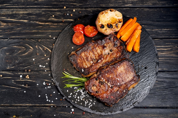 Juicy piece of fried meat lies on a stone plate against a black wooden table