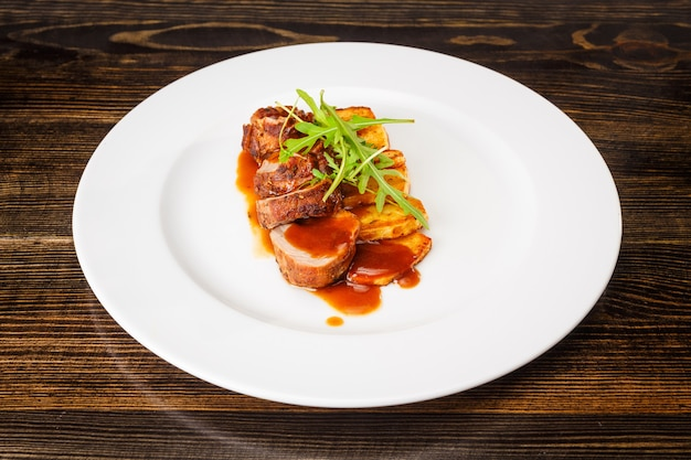 Juicy piece of grilled meat with fried potatoes and arugula on a white plate.