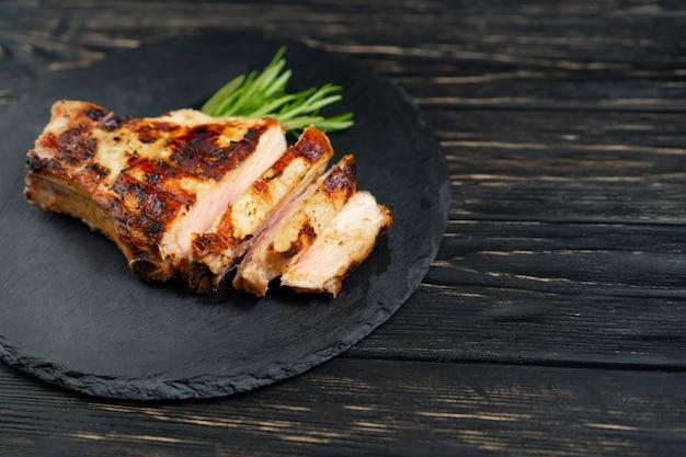 Сочный кусок жареного мяса лежит на каменной плите на черном деревянном столе