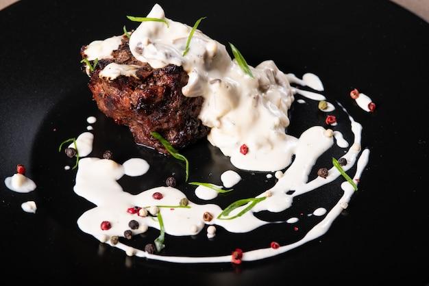 Сочный кусок мяса со сливочным соусом крупным планом
