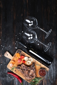 まな板の上にのせたジューシーなステーキ、野菜のグリル、ワインのボトル、グラス2杯