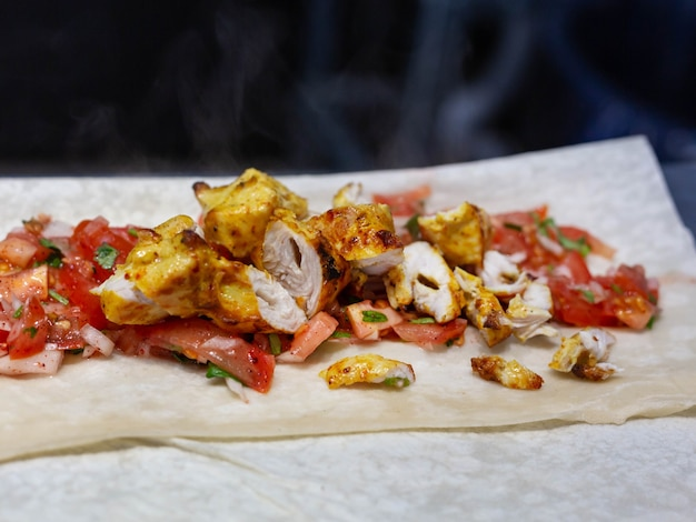 Juicy pieces of chicken kebab lie on thin pita bread along with chopped vegetables