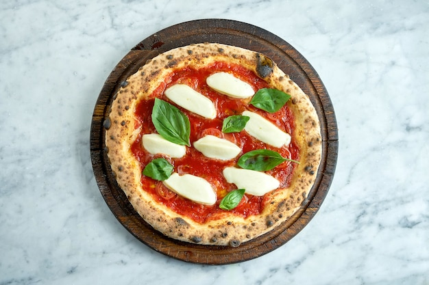 ジューシーなピザマルゲリータ、レッドソース、トマト、クリーミーなモッツァレラチーズ、バジル。大理石のテーブルの上の木の板の上の木製オーブンからのイタリアンピザ