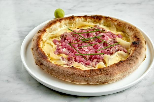 ホワイトソース、マグロ、クリームチーズ、生姜のジューシーなピザ。大理石のテーブルの上の木の板の上の木製オーブンからのシーフードとイタリアンピザ