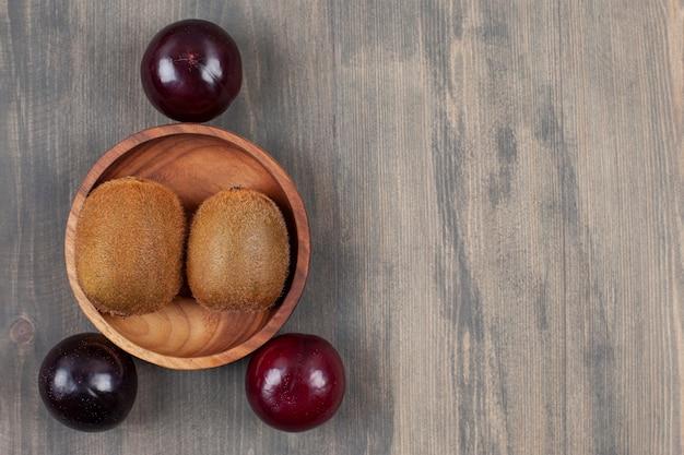 木製のテーブルにキウイとジューシーなプラム。高品質の写真