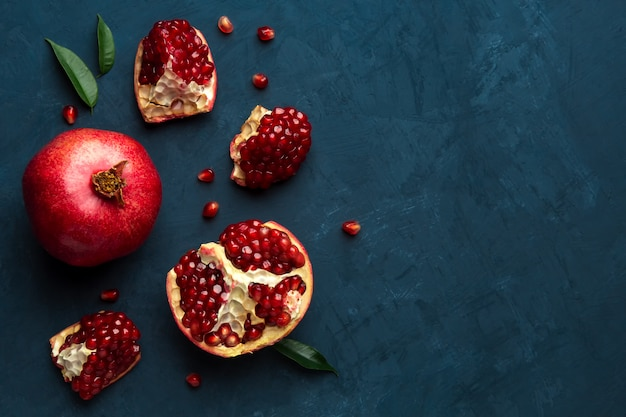 Juicy pomegranate on blue with place for text