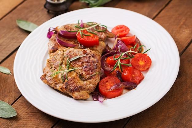 Сочный стейк из свинины с розмарином и помидорами на белой тарелке