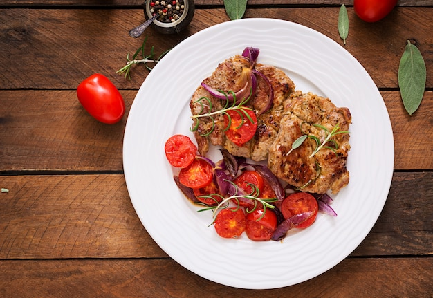 Juicy pork steak with rosemary and tomatoes on a white plate.
