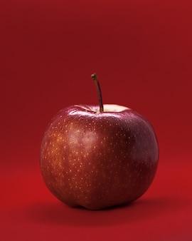 Сочное красное яблоко на красном фоне. темный свет. концепция цвета, страсти, здорового питания. крупным планом фото фруктов