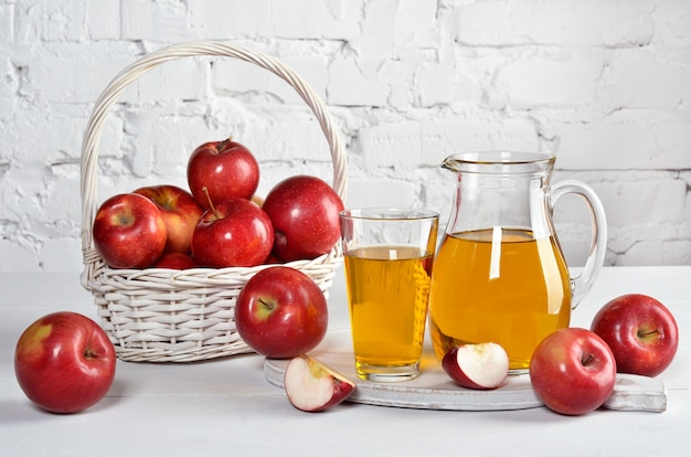 Juicy red apples in glass and carafe, basket with  apples on white table against the background of  white wall.  ãƒâƒã'âãƒâ'ã'â¡opy space.