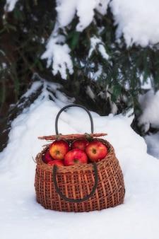 冬の雪に覆われた森の木の下の籐のかごの中のジューシーな赤いリンゴ