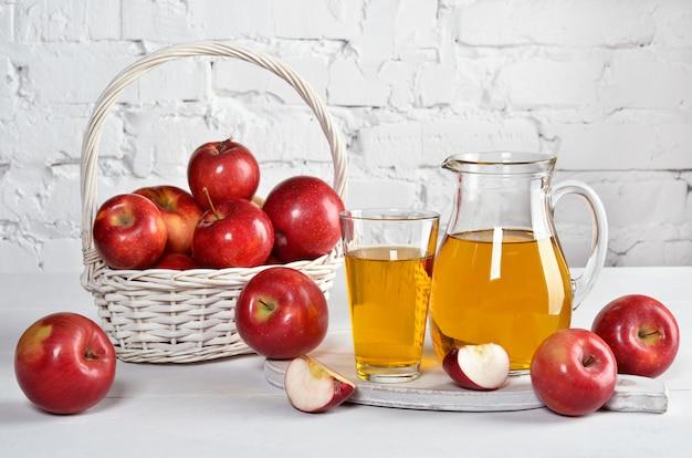 Сочные красные яблоки в стекле и графине, корзина с яблоками на белом столе на фоне белой стены. копирование пространства.