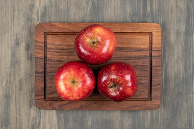 나무 절단 보드에 수 분이 많은 빨간 사과. 고품질 사진