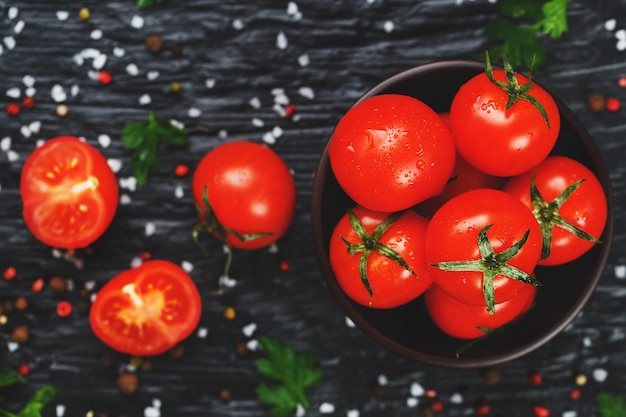 Juicy red cherry tomatoes with spices, coarse salt and greens. sweet and ripe tomatoes for salads and as ingredients for cooking