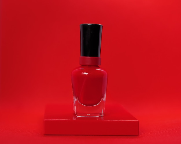 赤い背景にジューシーな赤いマニキュア。ハンドケア、広告マニキュアサロン、マニキュア、美しいネイル、化粧品のメーカーのコンセプト。クローズアップ写真。