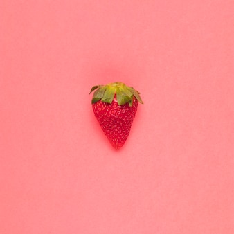 Juicy red strawberry on pink background