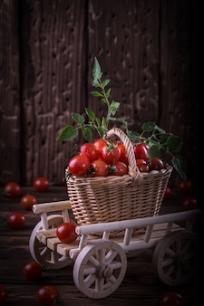 Juicy red tomatoes in basket on wooden table