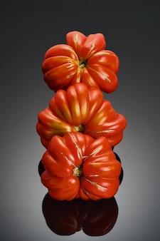 Succosi pomodori rossi della varietà lorena con struttura a coste da vicino, messa a fuoco selettiva. pomodori isolati su sfondo scuro, verdure di stagione sane dal mercato degli agricoltori, banner