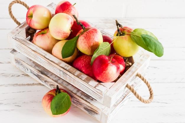 Сочные спелые яблоки в коробке на белом деревянном столе.