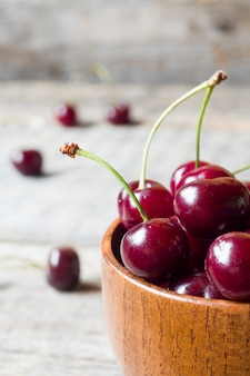 Juicy ripe cherries with sprigs in a wooden bowl