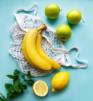環境にやさしい買い物袋に入ったジューシーで熟した柑橘系の果物とバナナ