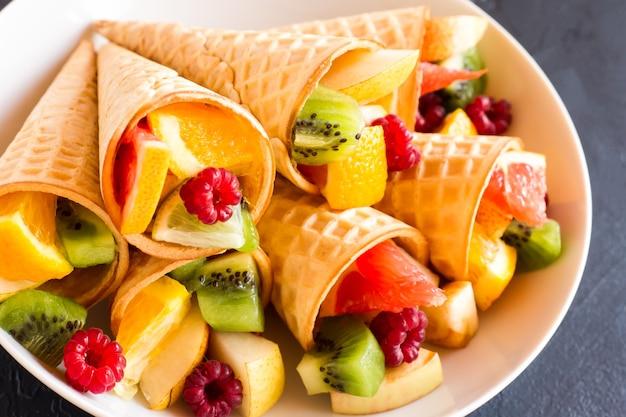 Сочные спелые фрукты в вафельных рожках на белой тарелке. близкий угол.