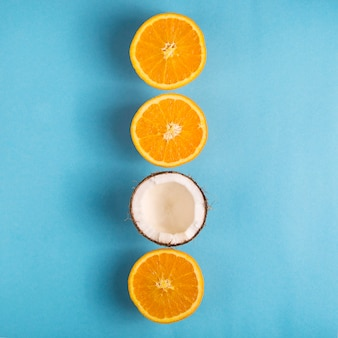 Juicy ripe oranges and open coconut on a bright blue background