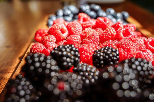 Juicy ripe organic berries on a wooden plate