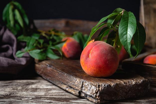 Сочный спелый персик на темной деревянной деревенской доске. вкусные фермерские персики с листьями натюрморт персик