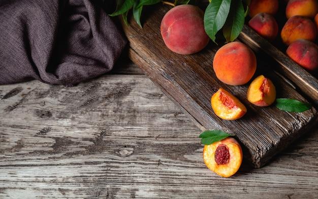 コピースペースのあるダークウッドの素朴なテーブルにジューシーな熟した桃。果物全体を半分にしたおいしい農場の桃、骨のある桃。静物ピーチダークキー。熟した桃の果実と木製のテーブル