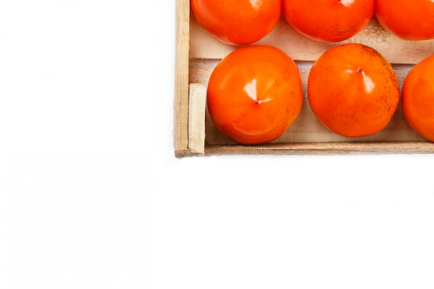 Juicy ripe persimmon in a large wooden box on white