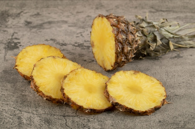Juicy ripe pineapple with its crown placed on stone surface.
