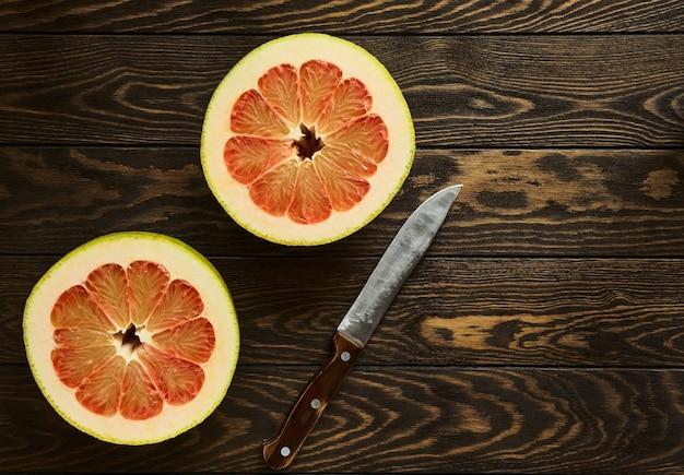 Juicy ripe red grapefruit cut in half lies on wooden table