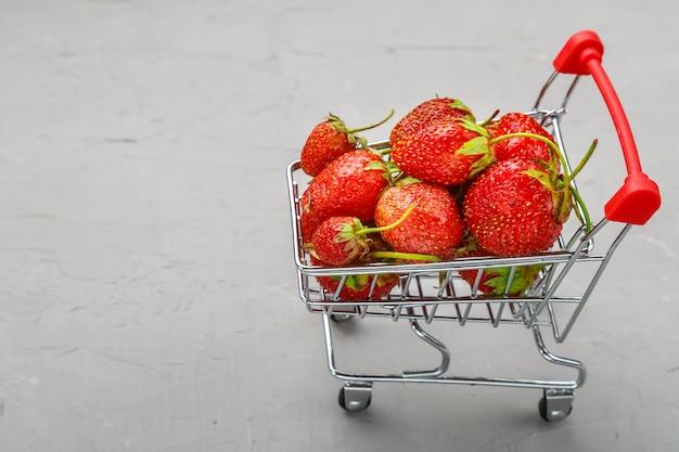 회색 배경에 식료품 카트에 즙이 많은 익은 딸기.