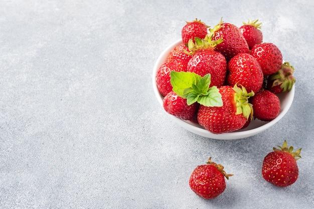 コンクリートの背景のプレートにジューシーな熟したイチゴ。甘くてヘルシーなデザート、ビタミンの収穫。コピースペース。