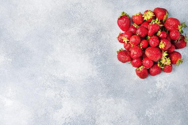 コンクリートの背景にジューシーな熟したイチゴ。甘くてヘルシーなデザート、ビタミンの収穫。コピースペース。