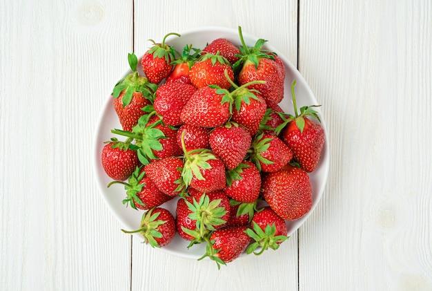 흰색 배경에 육즙, 익은 딸기. 상위 뷰, 클로즈업입니다. 여름 딸기입니다.
