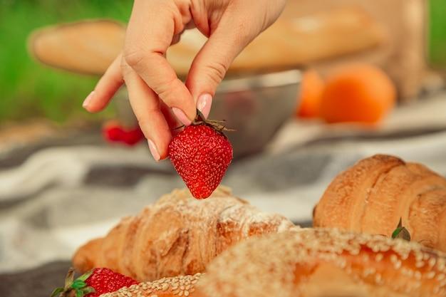 若い女性の手でジューシーな熟したイチゴ手夏のピクニックコンセプトクロワッサンと木製のベーグル