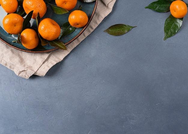 Сочные спелые мандарины с листьями на столе