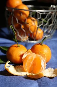 Сочные спелые мандарины с листьями на скатерти