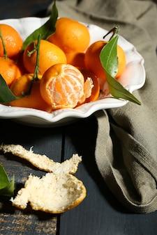 Сочные спелые мандарины с листьями на деревянном столе
